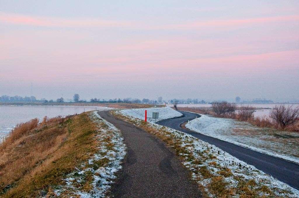 Kronkelende lijnen van de dijk en de weg naast de dijk, die naar de horizon voeren. Nikon D90 • ISO 1600 • f/8 • 1/50 @ 35mm.
