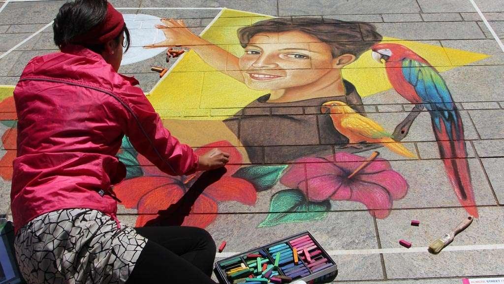 De tekenaar zit links onderin en kijkt over haar werk rechts in beeld. Zo krijgt de kijker een goed beeld van waar de tekenaar mee bezig is.